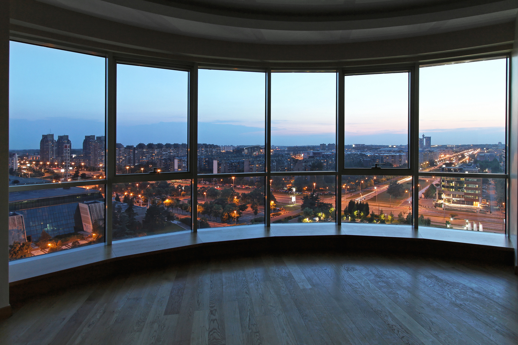 Big glass wall in oval living room with cityscape view